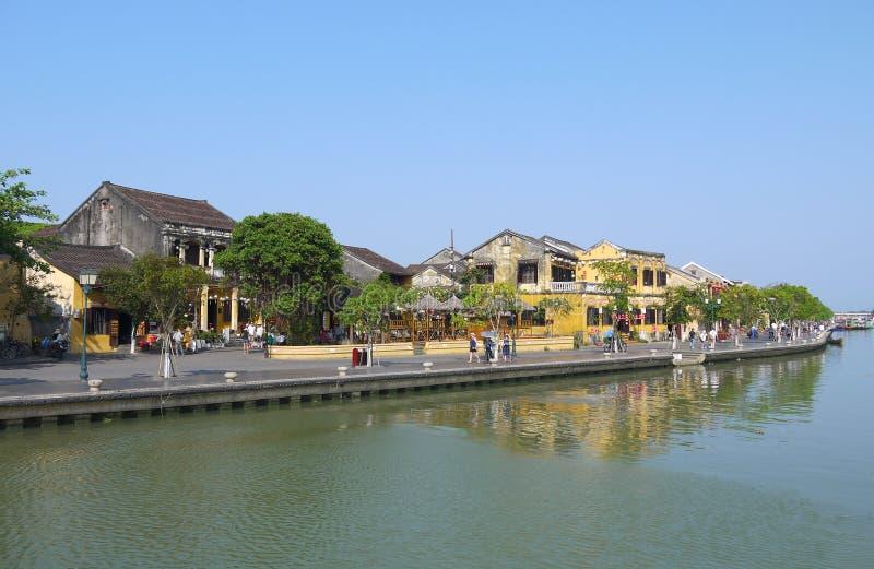 Lokalni ludzie, łodzie, kolorów żółtych domy rzeką i turyści w Hoi, antyczny miasteczko obrazy royalty free