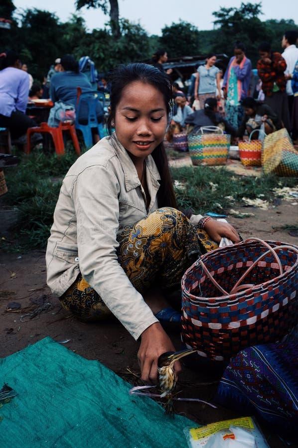 lokalni młodej kobiety sprzedawania ptaki przy wioską wprowadzać na rynek fotografia stock