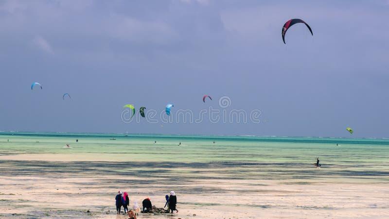 Lokalni rybacy i odwiedzać kania surfingowów przy Jamibiani plażą, Zanzibar obraz stock