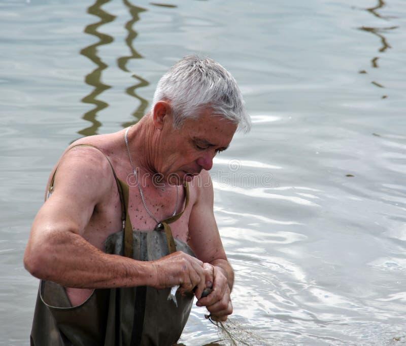 Lokalny mężczyzna łowi z siecią podczas powodzi w ogródzie fotografia stock