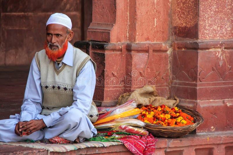 Lokalny mężczyzna sprzedawanie kwitnie w podwórzu Jama Masjid w sadle obraz royalty free