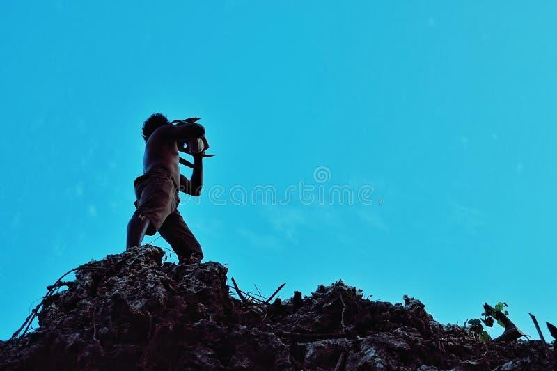 lokalny młody plemię członek dmucha jego bubu skorupy róg w tropikalnej tropikalny las deszczowy dżungli na wierzchołku rockowa k obrazy stock