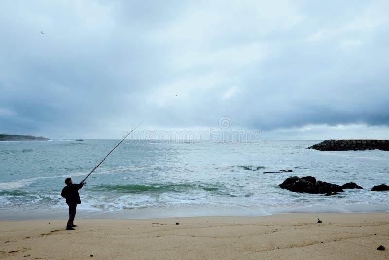 lokalny rybaka wędkarz ciska jego nęcenie przy piaskowatą brzeg plażą na atlantyckim oceanie zdjęcia royalty free