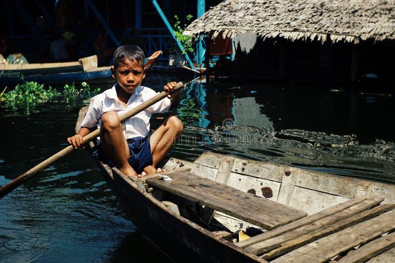 lokalny szkolnej chłopiec studencki paddling dom po klasy przy jeziorem na jego czółnie przed spławową stilt domu ugodą zdjęcia stock