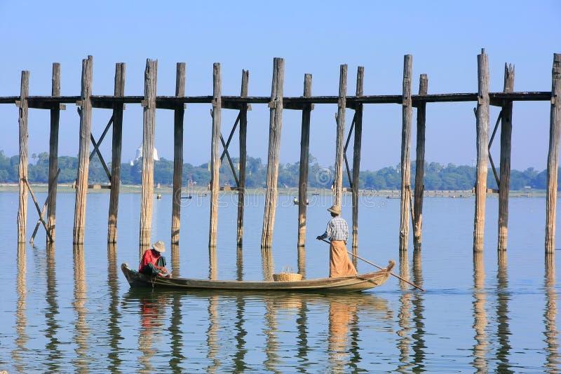 Lokalt folk som fiskar från ett fartyg nära bron för U Bein, Amarapura, arkivfoton