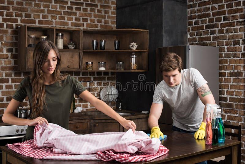lokalvård för den unga mannen och kvinnabordlägger tillsammans i kök fotografering för bildbyråer