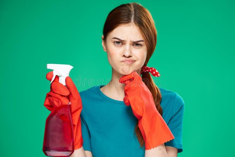 Lokalvård kvinna med ett rengöringsmedel, kvinna i röda handskar, på en grön bakgrund arkivbilder