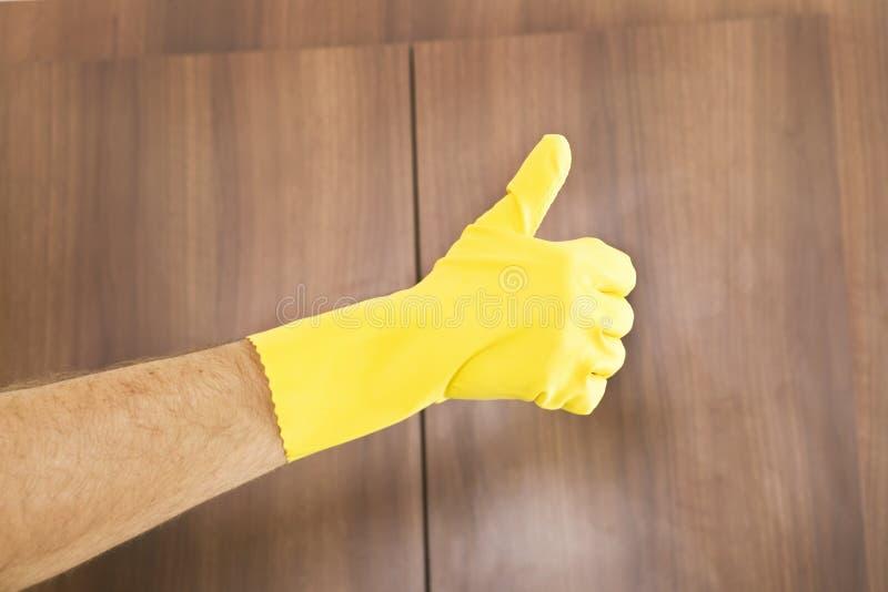 Lokalvårdframgång Tummar upp av handen i gul skyddande handske arkivbilder