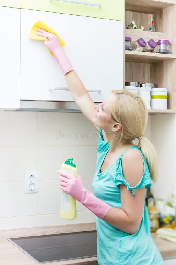 Lokalvårdmöblemang för ung kvinna i köket arkivbilder