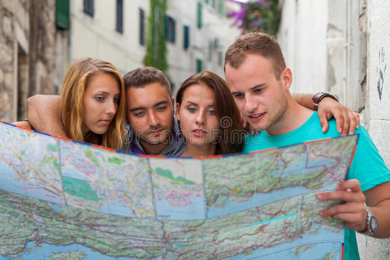 loking在街道上的地图的朋友 他们是在度假 库存照片