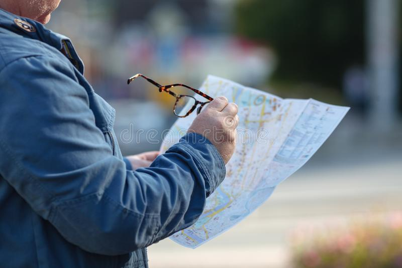 loking在街道上的地图的游人,在度假 免版税库存图片