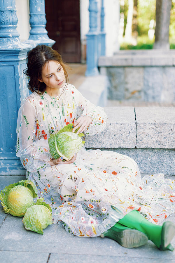 lokking美丽的女孩坐在房子附近用许多圆白菜和在旁边 俏丽的女孩时尚画象用圆白菜 女孩和 免版税图库摄影