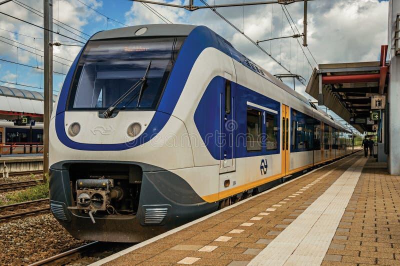 Lokomotoryczna przerwa na dworzec platformie, linia kolejowa poręczach i błękitnym chmurnym niebie przy Weesp, fotografia stock