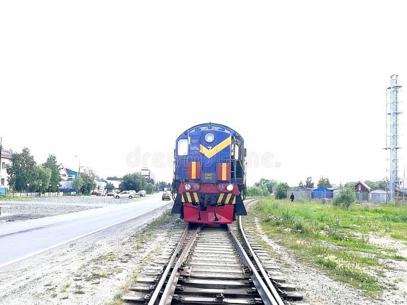 Lokomotoryczny pociąg błękitny kolor jedzie wzdłuż poręczy w strefie przemysłowej miasto zdjęcia royalty free