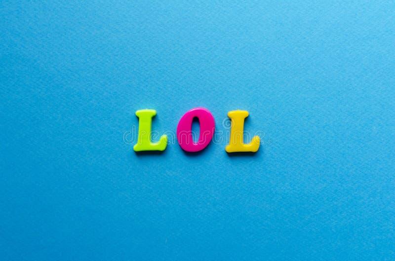 Lol d'abréviation des lettres magnétiques en plastique sur le fond bleu images libres de droits