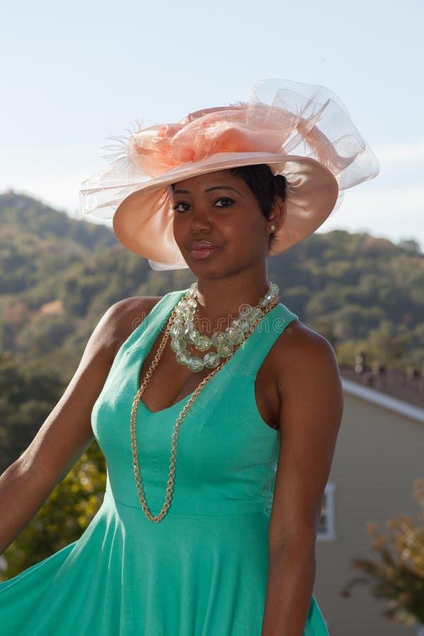 Lola, die südliche Schönheit mit rosa Hut und grünem Kleid stockbild