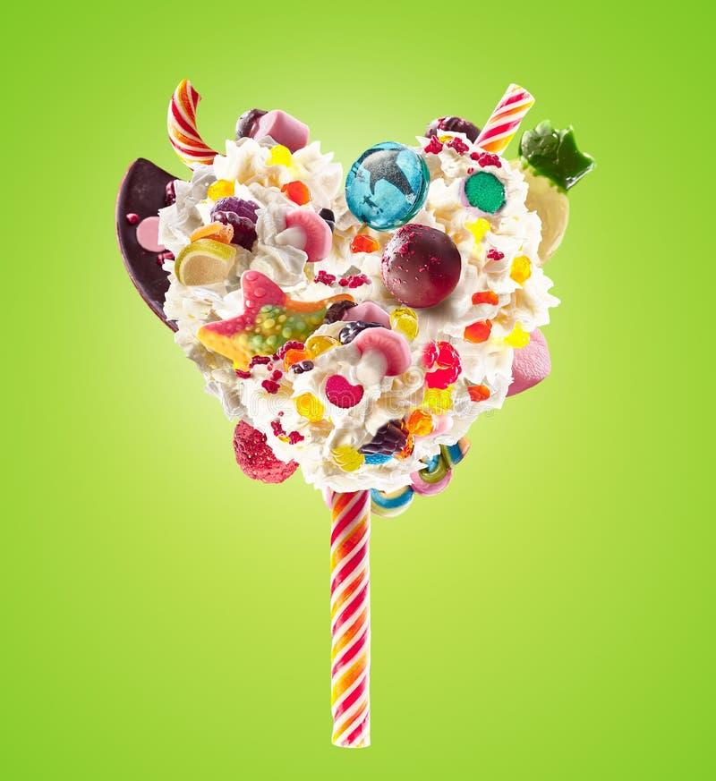 Lolipop dolce nella forma del cuore di panna montata con i dolci, gelatine, vista frontale del cuore Tendenza pazza dell'alimento fotografia stock