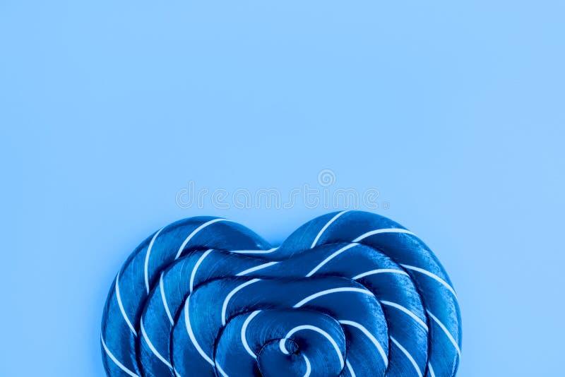 Lollipop on blue background. Flat lay. Minimal concept. stock photo