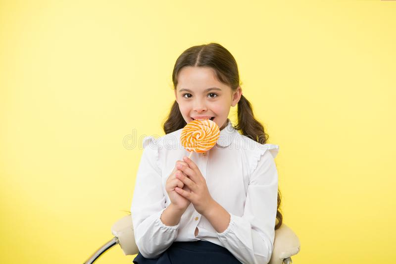 Lollipop child. child eating lollipop in yellow studio. lollipop child eating candy with happy face. child lick sweet. Lollipop candy. having fun with candies stock image