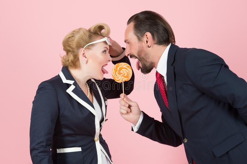 Lollipop in danger from two managers on pink background stock photos