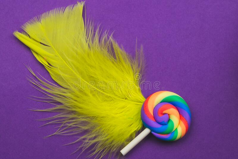 Lollipop lies on a feather. spiral candy on a colored background. festive decoration. Copy space stock photography