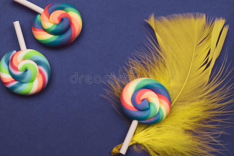 Lollipop lies on a feather. spiral candy on a colored background. festive decoration. Copy space royalty free stock image
