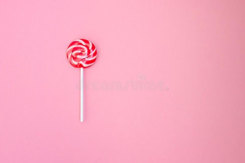 Lollipop Pirulito listrado em um fundo delicadamente cor-de-rosa Listras vermelhas e brancas nos doces fotos de stock