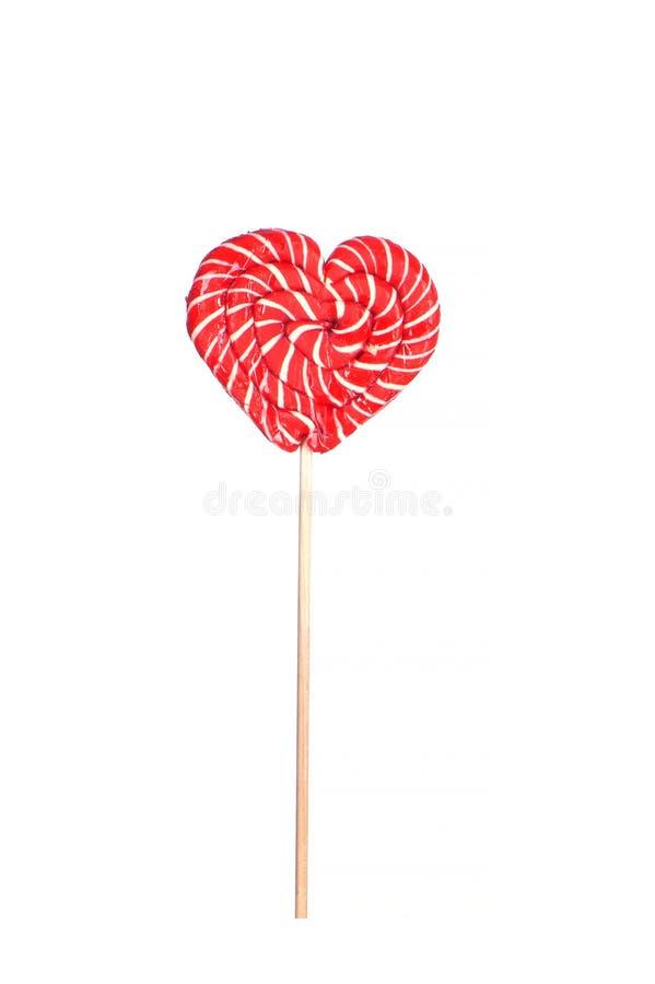 Lollipop rouge sur un bâton en forme de coeur isolé sur blanc image stock