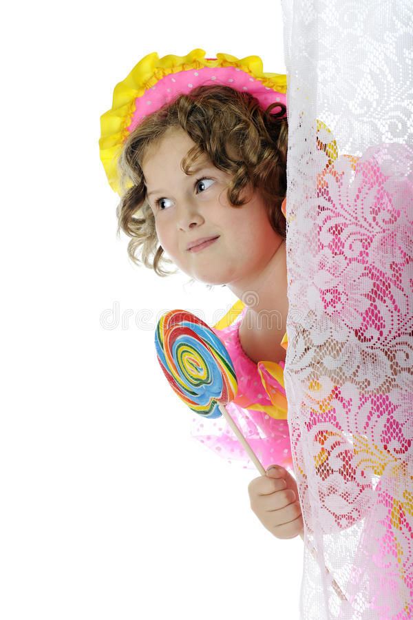 Lollipop Sneak. A sneaky elementary girl happily peeking out from behind a lace curtain with her giant-sized lolli pop. On a white background stock photos