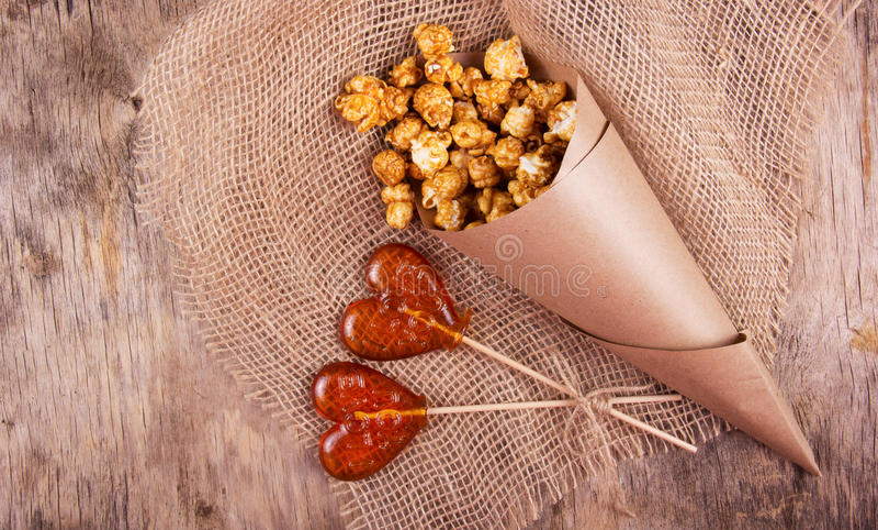 Lolly twee in de vorm van een hart en een document zak karamelpopcorn op houten achtergrond royalty-vrije stock foto's