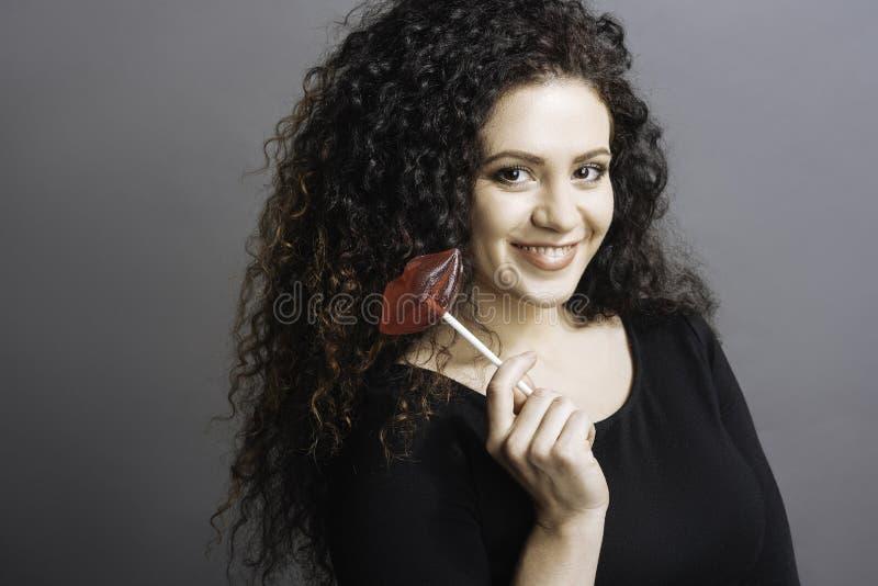 Lollypop de mantimento fêmea novo encantador no assistente fotos de stock