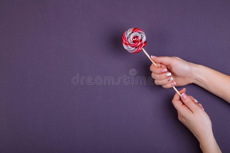 Lollypop på en pinne i hand royaltyfria foton