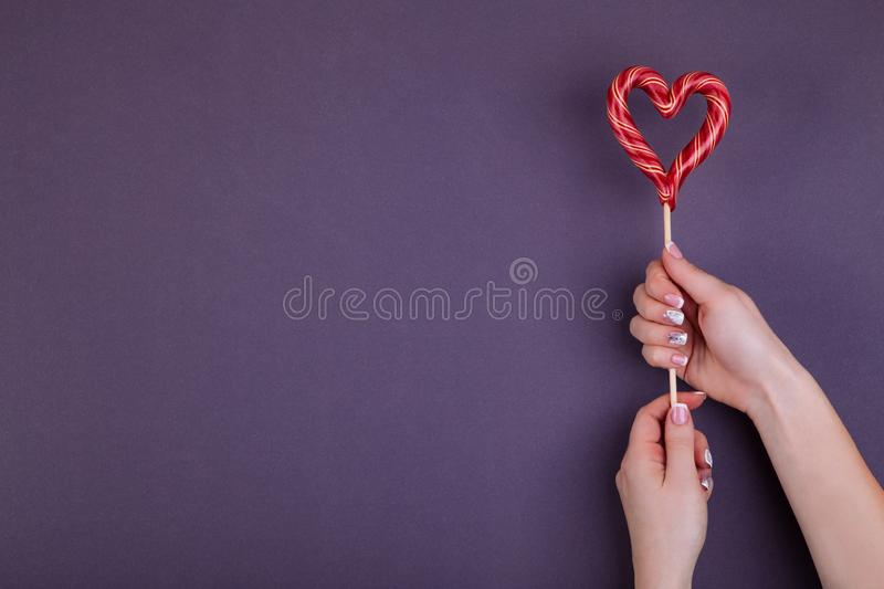 Lollypop on a stick in hand. Red hart shaped lollypop on a stick in female hands. Concept of stylish french manicure. Flat lay style stock photos