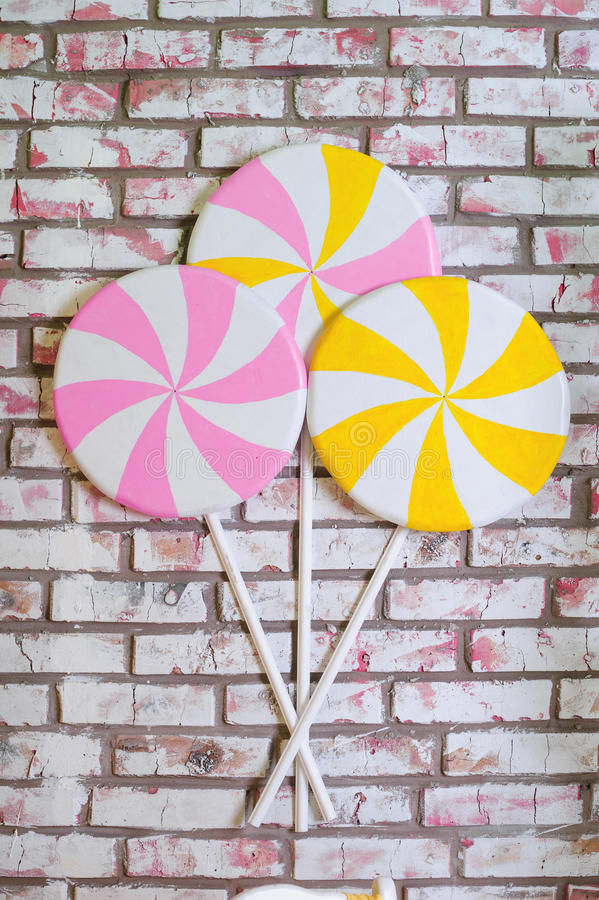 Lollypops multicolores en el fondo de la pared de ladrillo fotografía de archivo libre de regalías