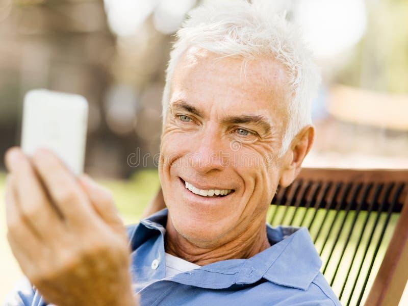 Download LoMature Man Som Använder Utomhus Mobiltelefonen Arkivfoto - Bild av kommunikation, holding: 78728676