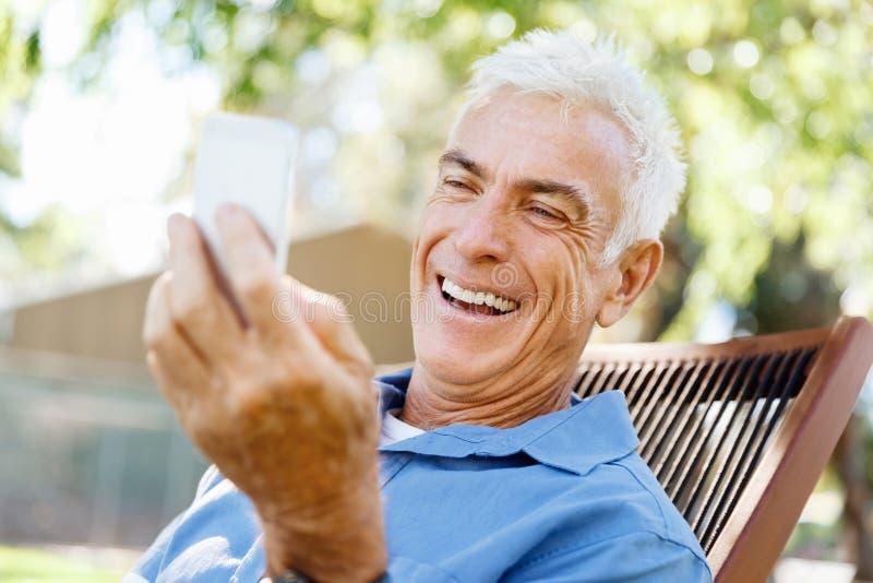 Download LoMature Man Som Använder Utomhus Mobiltelefonen Arkivfoto - Bild av frankt, utomhus: 78729976