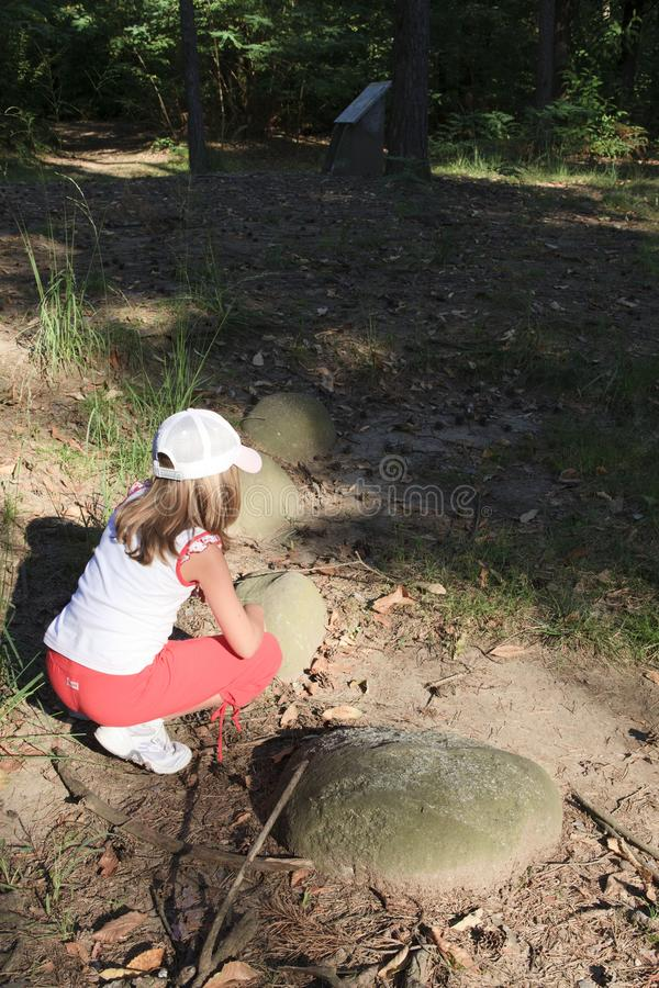 Lombardia. Golasecca VA, Italy - September 15, 2016: A child looks necropolis ruins at The Monsorino archaeological site, Golasecca, Varese, Lombardy, Italy royalty free stock photography