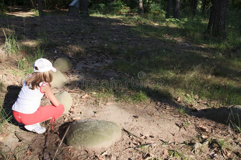 Lombardia. Golasecca VA, Italy - September 15, 2016: A child looks necropolis ruins at The Monsorino archaeological site, Golasecca, Varese, Lombardy, Italy stock photos