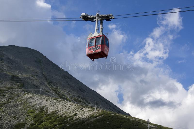 Lomnicky stit, High Tatra mountains / SLOVAKIA - July 6, 2017: Amazing aerial lift full of tourists from station Skalnate pleso to stock photo