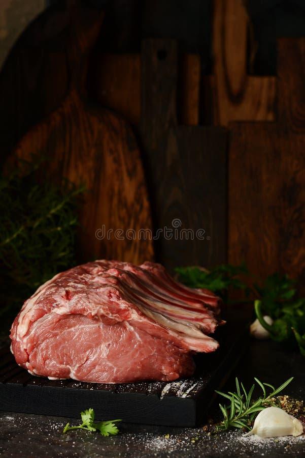 Lomo de cerdo crudo fresco en el hueso en un tablero de madera con las hierbas, las especias y la sal del mar imagen de archivo libre de regalías