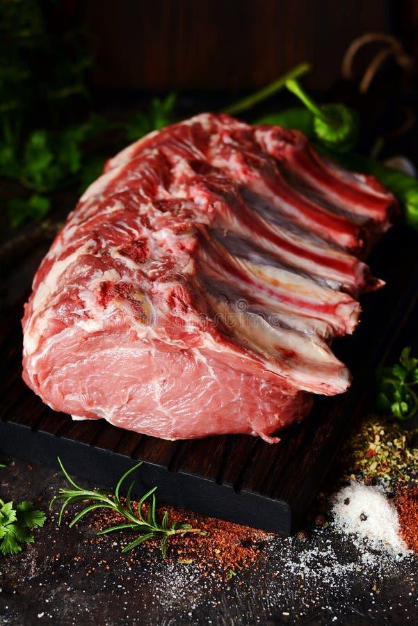 Lomo de cerdo crudo fresco en el hueso en un tablero de madera con las hierbas, las especias y la sal del mar fotografía de archivo