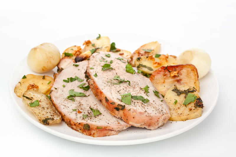 Lomo de cerdo de Roaste cortado con las patatas asadas foto de archivo libre de regalías
