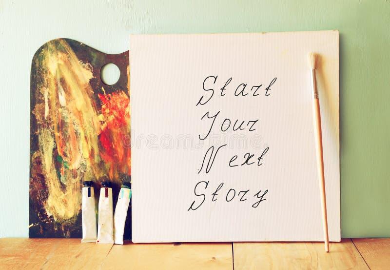 Lona con el comienzo de la frase su historia siguiente al lado de las pinturas y de la paleta de aceite fotos de archivo