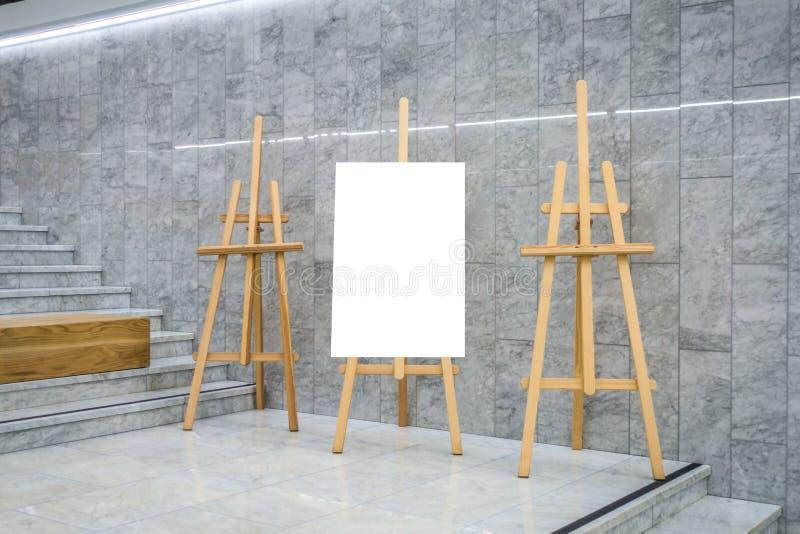 Lona en blanco del tablero del arte y tres caballetes de madera en galería de la exposición imagenes de archivo