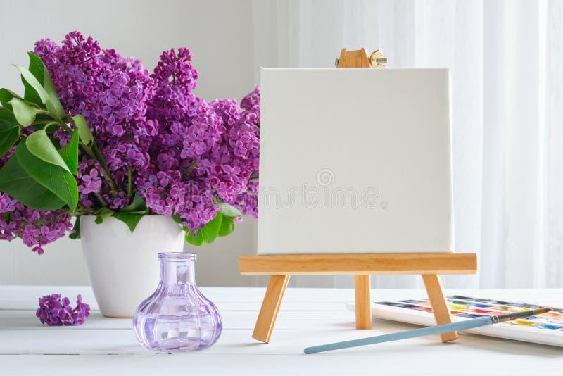 Lona en blanco en el caballete, las pinturas de la acuarela, el cepillo para la pintura y las flores de la lila en la tabla fotos de archivo libres de regalías