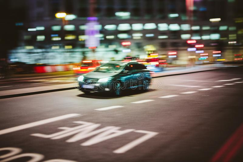 Lond at night with car driving fast on the street. Abstract defocused in motion British car driving fast to destination on the London street at night royalty free stock image