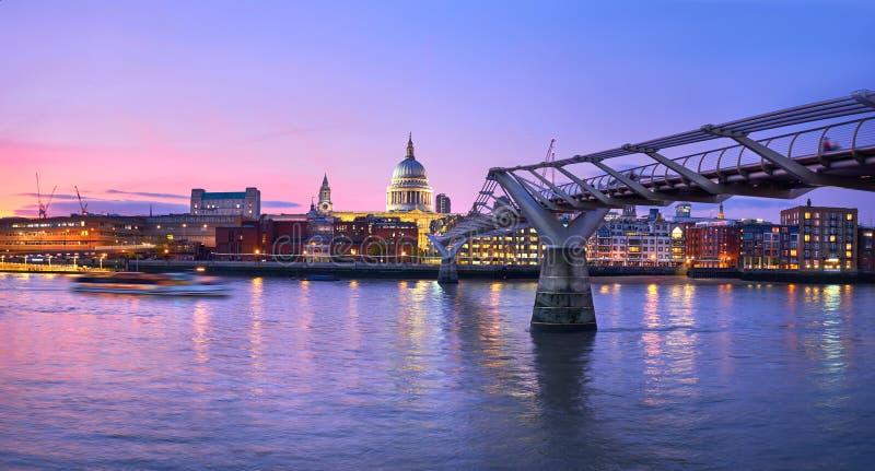 Londen bij zonsondergang, Millenniumbrug die naar verlicht leiden royalty-vrije stock foto