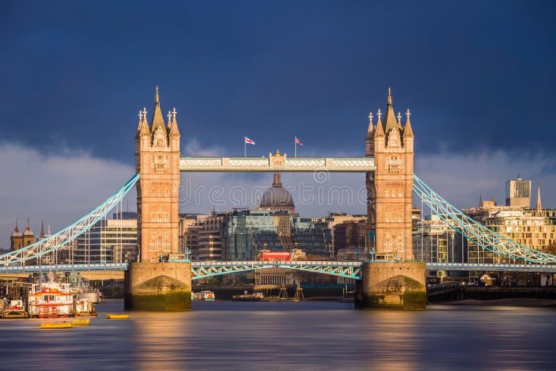 Londen, Engeland - de wereldberoemde Torenbrug bij gouden zonsopgang met rode dubbeldekkerbus stock foto