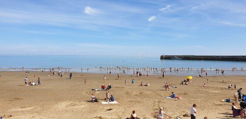 Londen, Engeland, Folkestone, Kent: 1 juni 2019: Toeristen die op Zonnig zandstrand van de mooie zonneschijn en van de blauwe hem stock fotografie