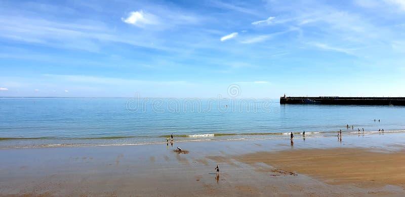 Londen, Engeland, Folkestone, Kent: 1 juni 2019: Toeristen die op Zonnig zandstrand van de mooie zonneschijn en van de blauwe hem royalty-vrije stock fotografie